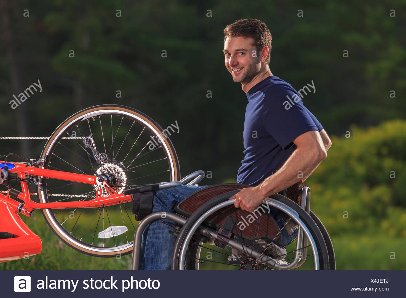 Man with spinal cord injury in his wheelchair with his custom adaptive hand cycle - Stock Image