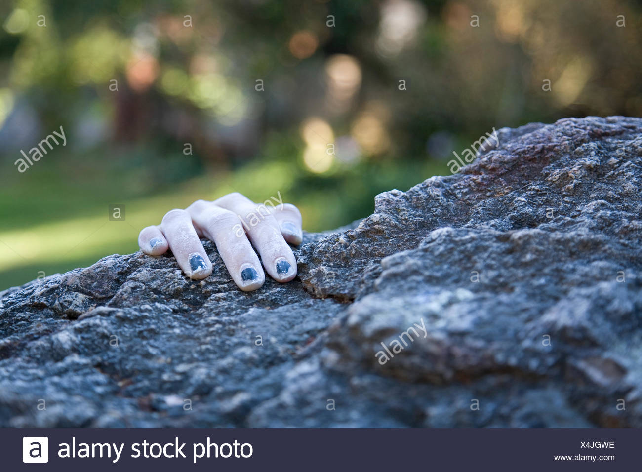 A climber's hand appears at the edge of a precipice during a bouldering session at Indian Rock in Berkeley, CA. - Stock Image