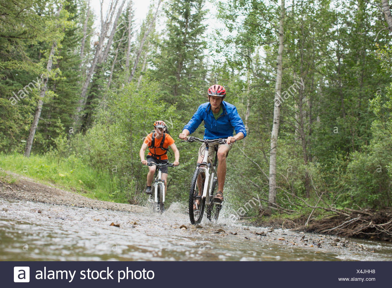 two male mountain bikers riding through stream - Stock Image