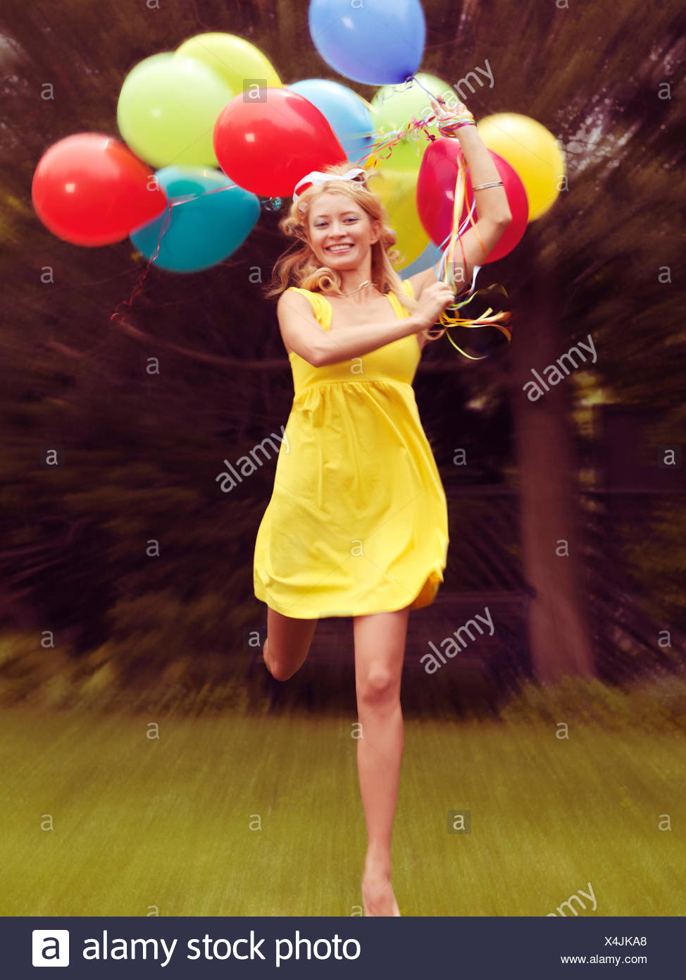 Happy young woman in summer dress running with colorful balloons - Stock Image