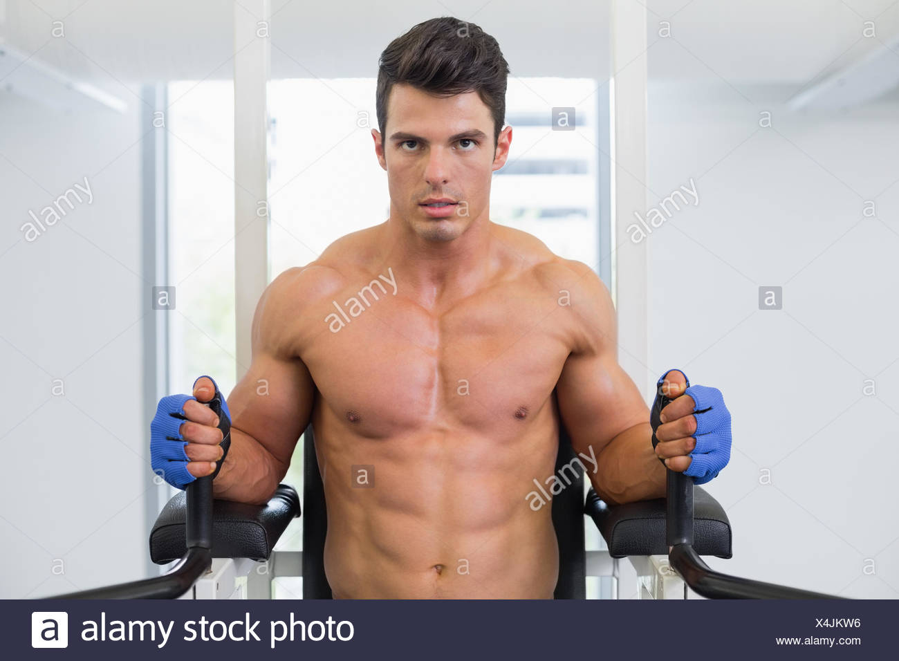 Muscular man doing crossfit fitness workout in gym - Stock Image