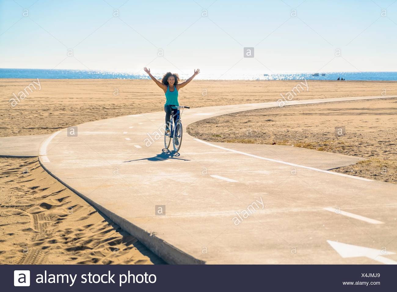 Mid adult woman cycling along pathway at beach, arms in air - Stock Image