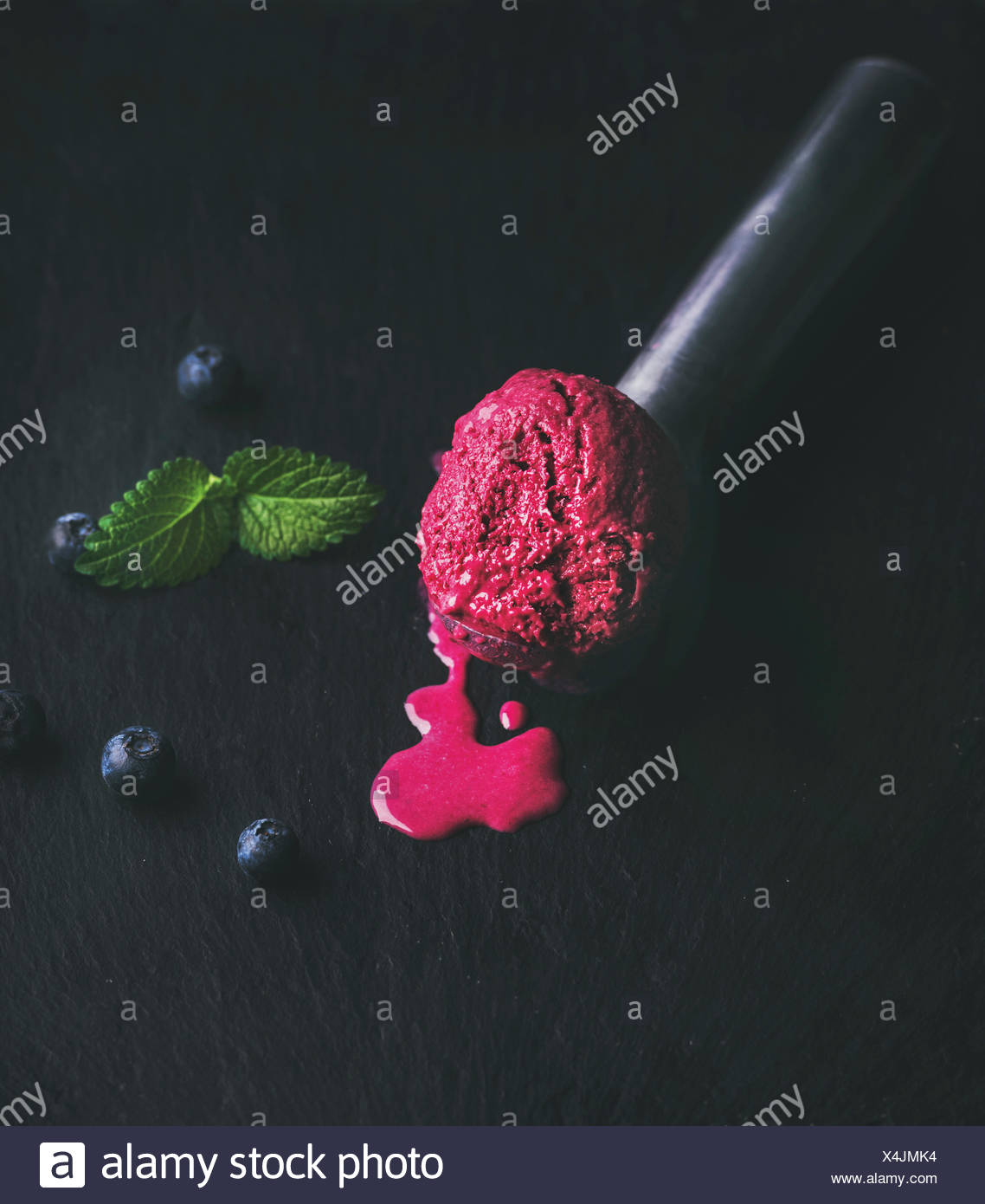 Melting scoop of blueberry ice-cream with mint leaves over black slate stone background, selective focus - Stock Image