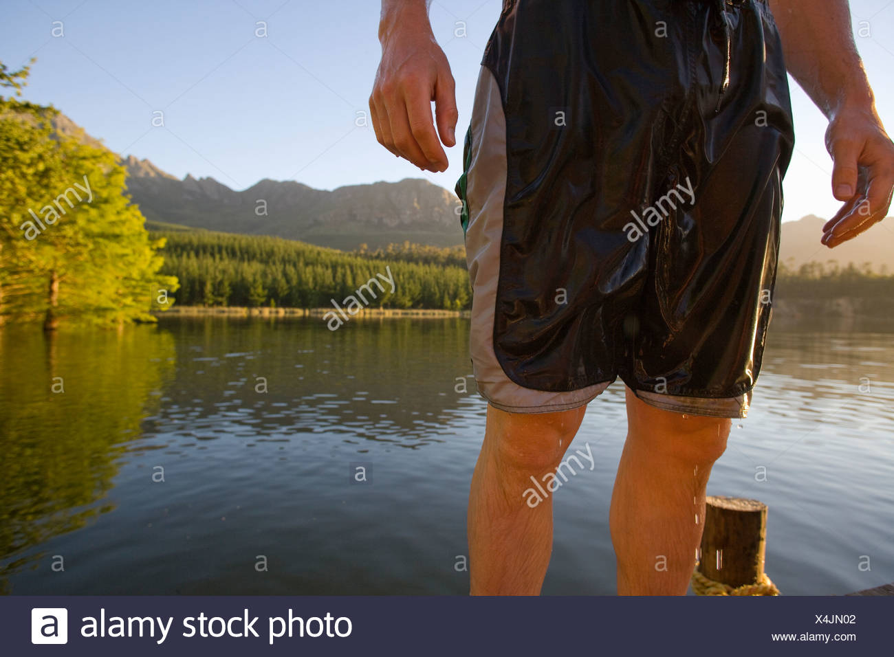 Midsection of man in wet swim trunks - Stock Image