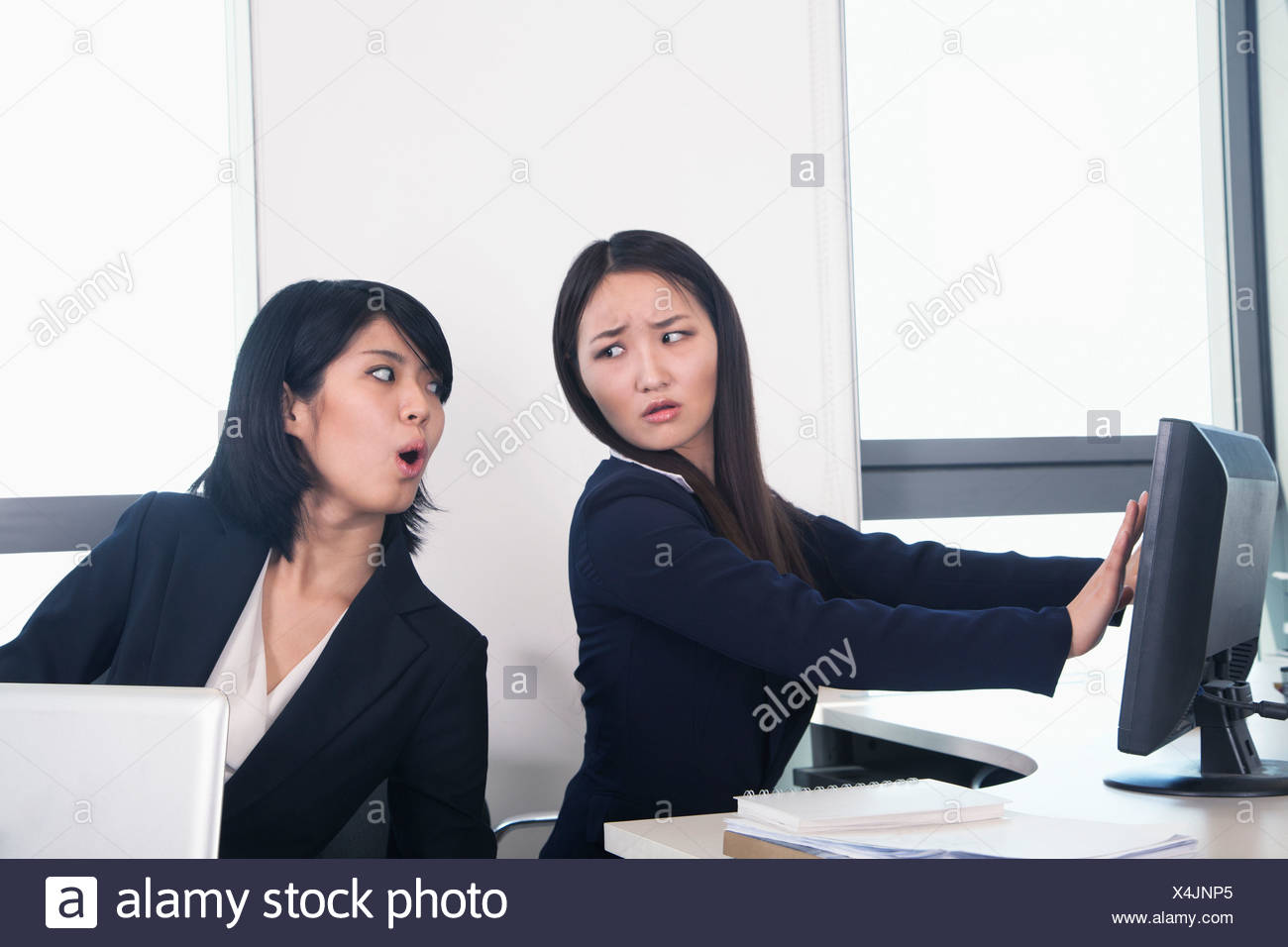 Officer worker hiding her computer from coworker - Stock Image