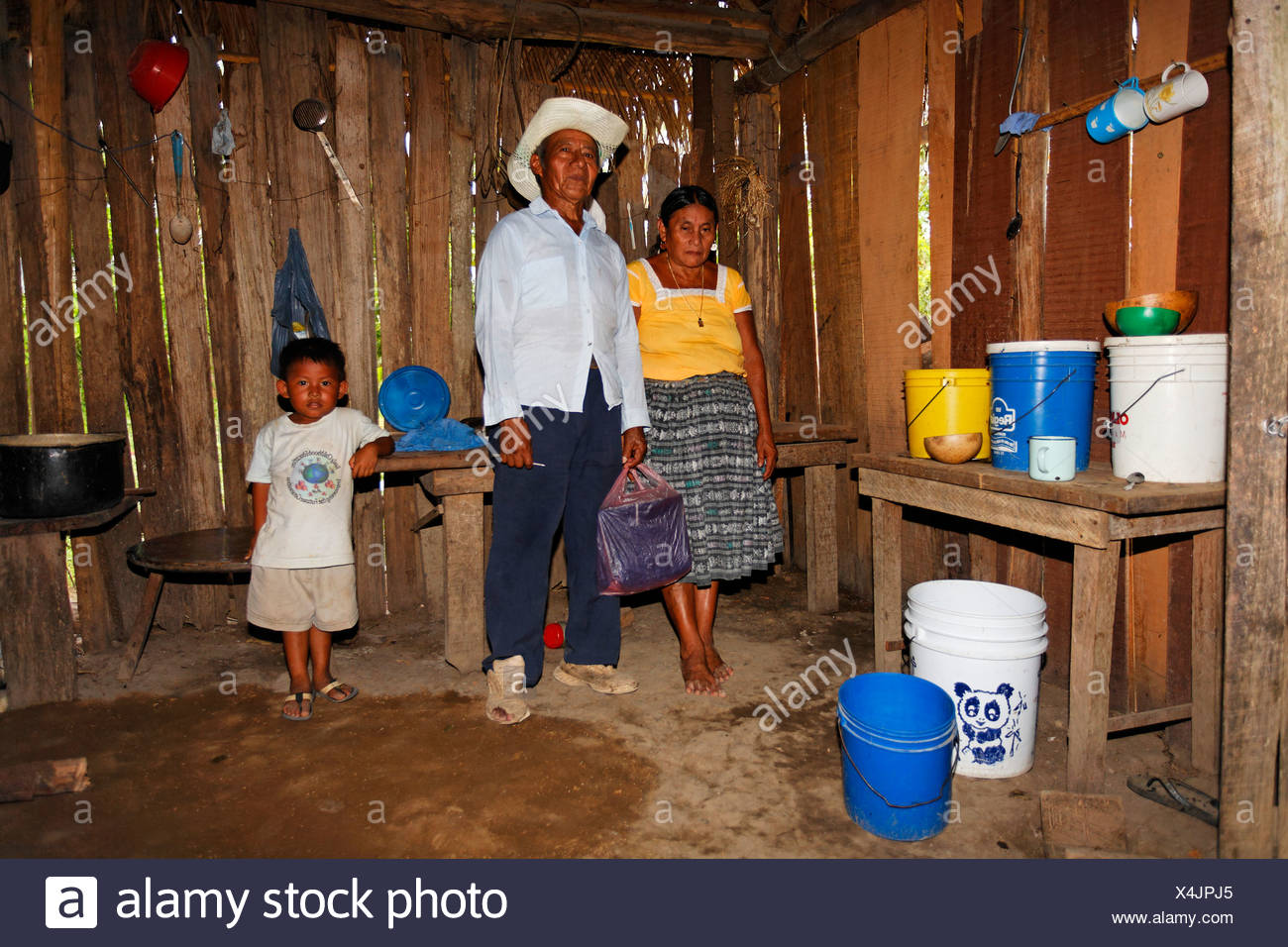 Mayan woman, man, small boy, one-room flat, plastic bucket, wooden hovel, Punta Gorda, Belize, Central America - Stock Image