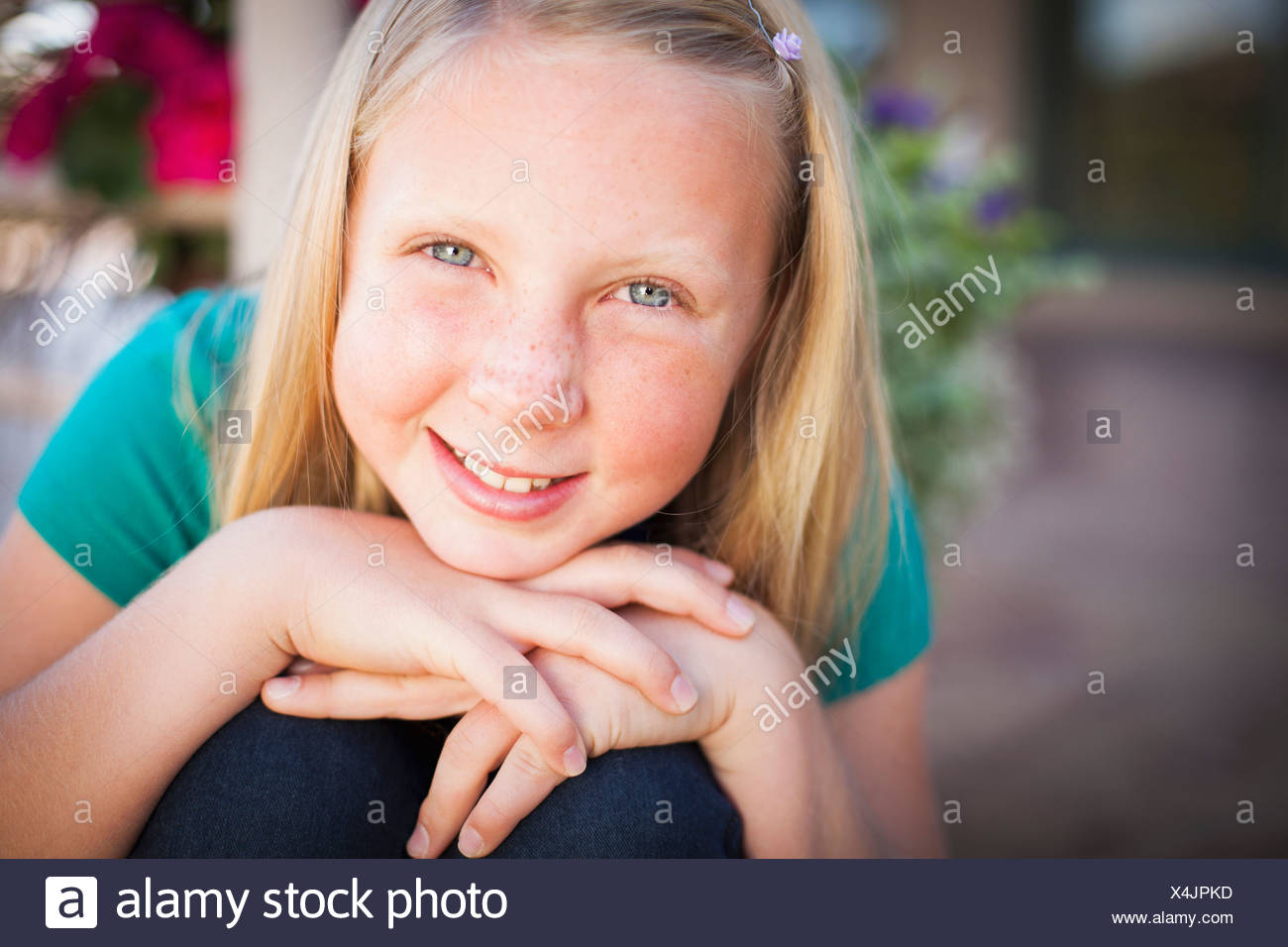 A child, a young girl sitting leaning forward and smiling. Her chin resting on her hands. - Stock Image