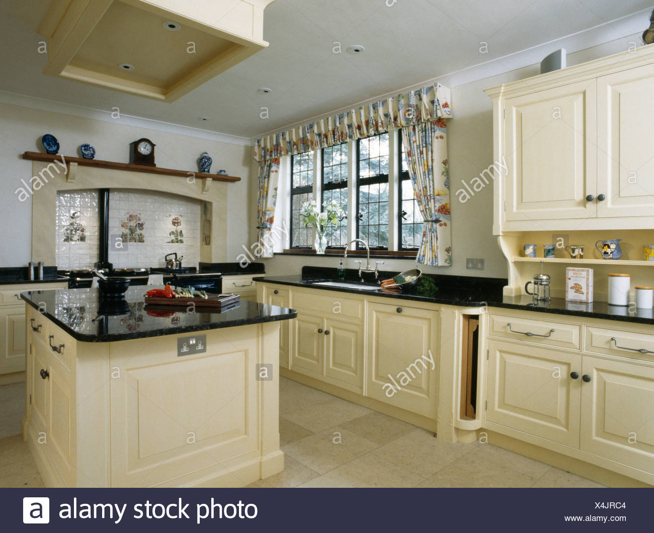 Cream Island Unit With Black Granite Worktop In Large Country Kitchen Stock Photo Alamy
