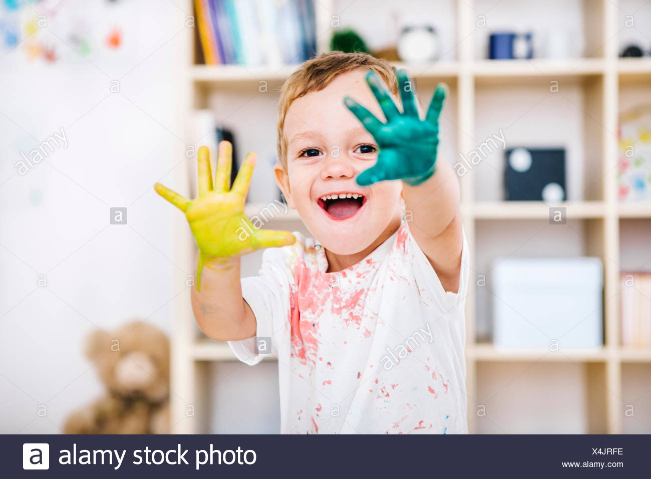 Portrait of smiling little boy showing his painted hands - Stock Image