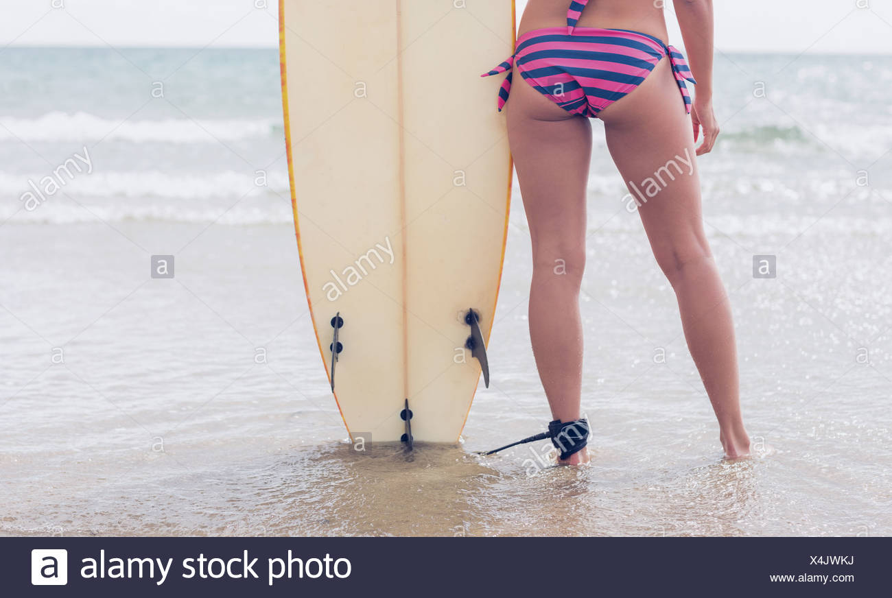 Slender woman in bikini bottom with surfboard on beach - Stock Image