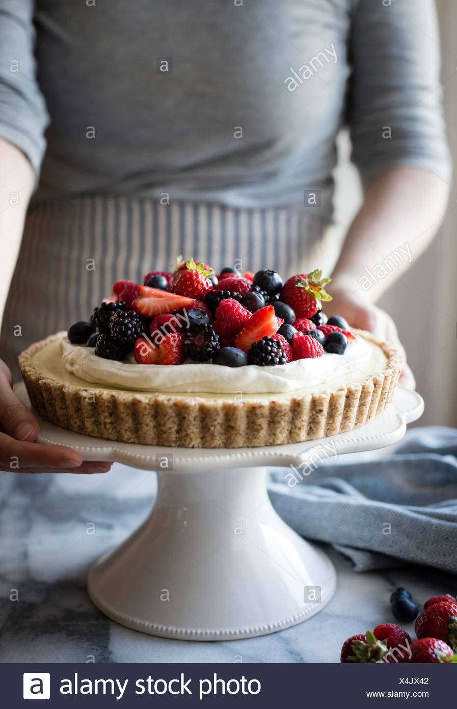 Woman with a No-Bake Lemon Berry Coconut Cream Tart with fresh berries (vegan, gluten-free, refined sugar-free) on a cake stand - Stock Image