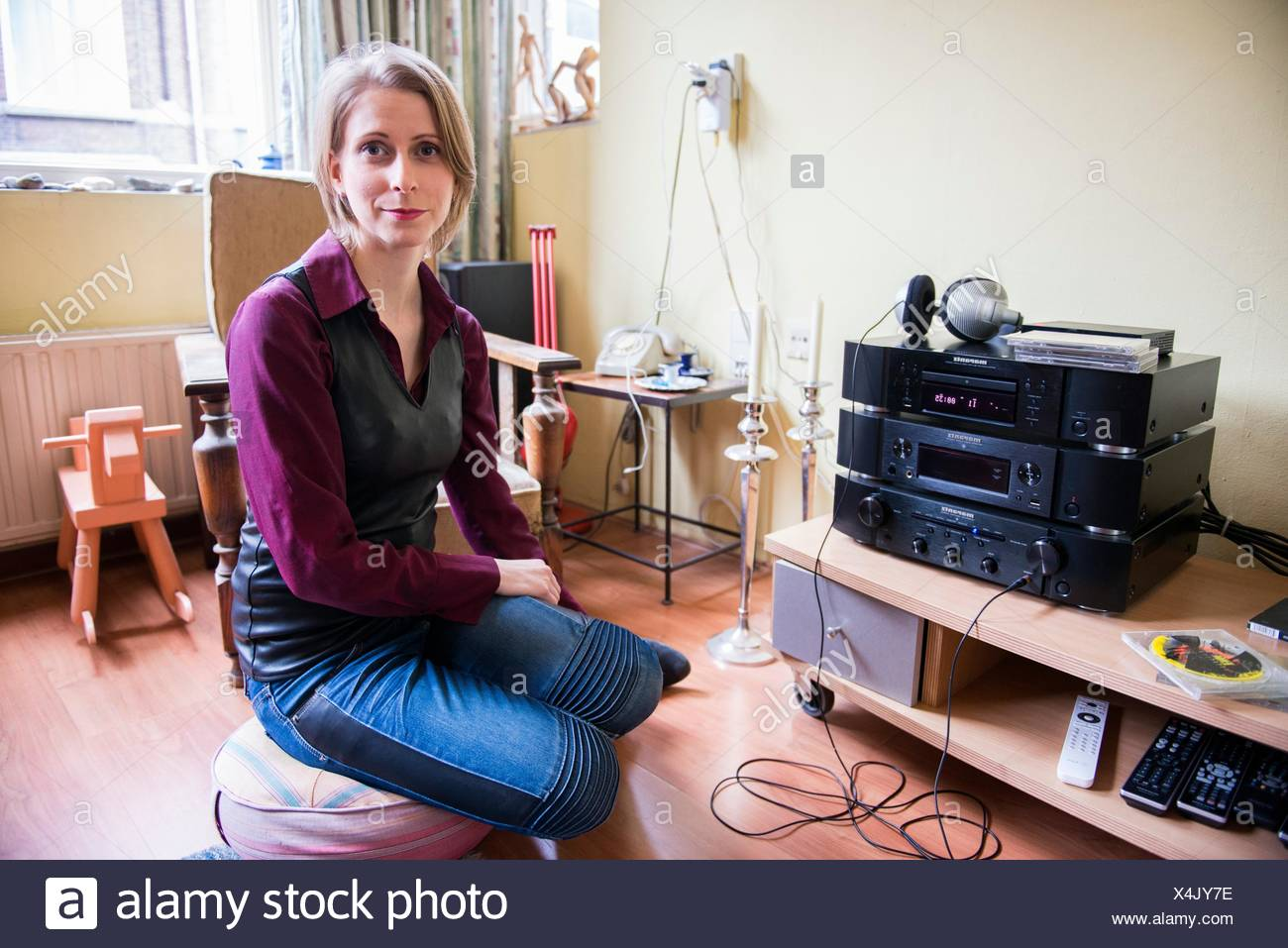 Tilburg, Netherlands. Young adult caucasian woman enjoying music from her stereo hifi set using a headset and a cd or compact disc. - Stock Image