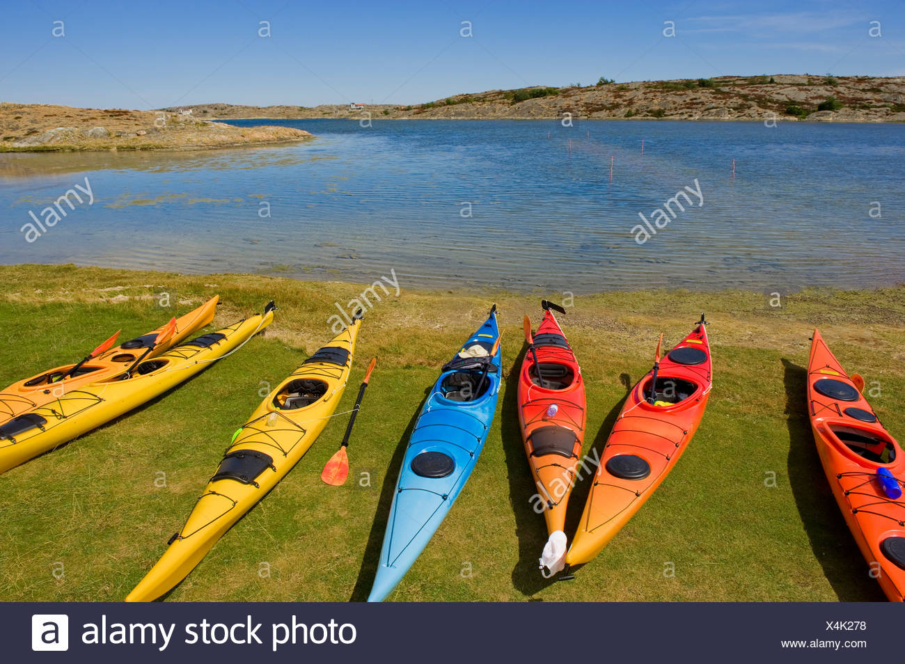 Several kayaks on grass by the calm sea - Stock Image
