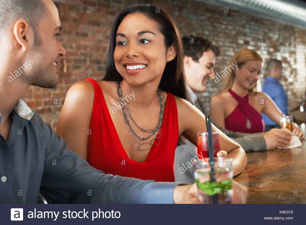 Couple holding cocktails, sitting at bar Stock Photo