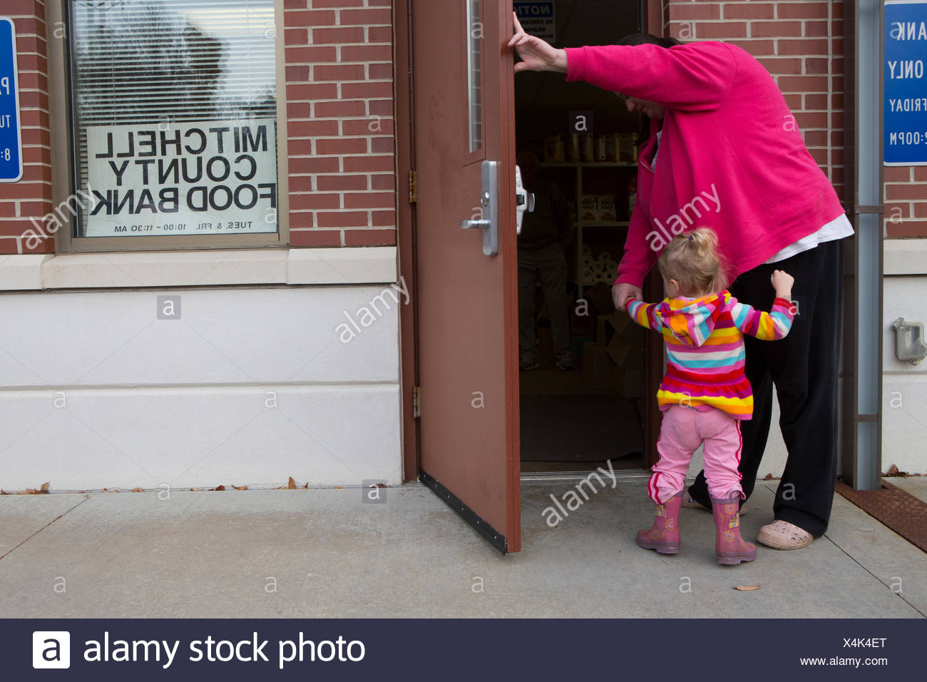 A woman arrives at the Mitchell County Food Bank in Osage, Iowa to receive donated food for her family. Stock Photo