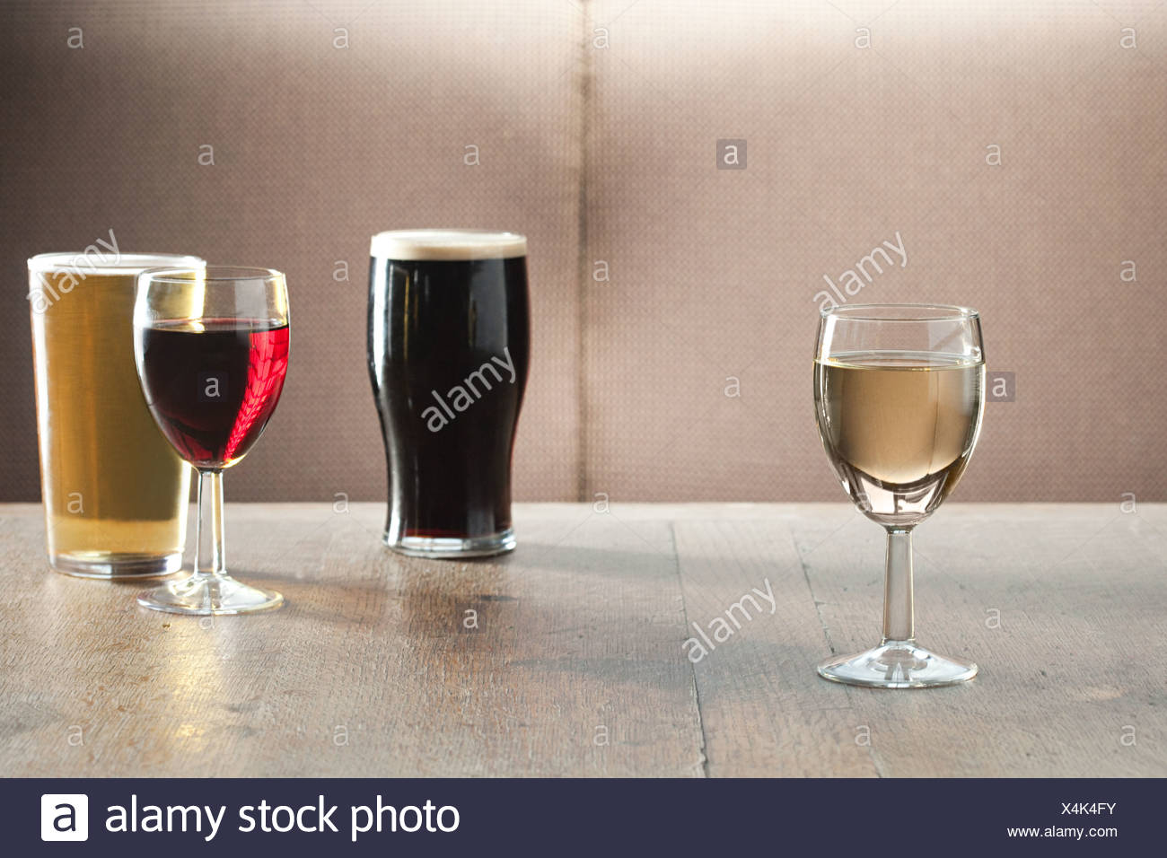 Wine and beer glasses on table in bar - Stock Image