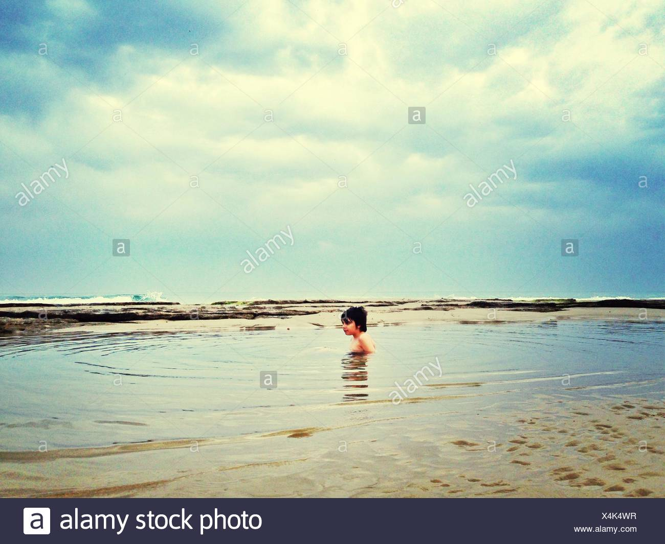 Shirtless Boy Swimming In Sea - Stock Image