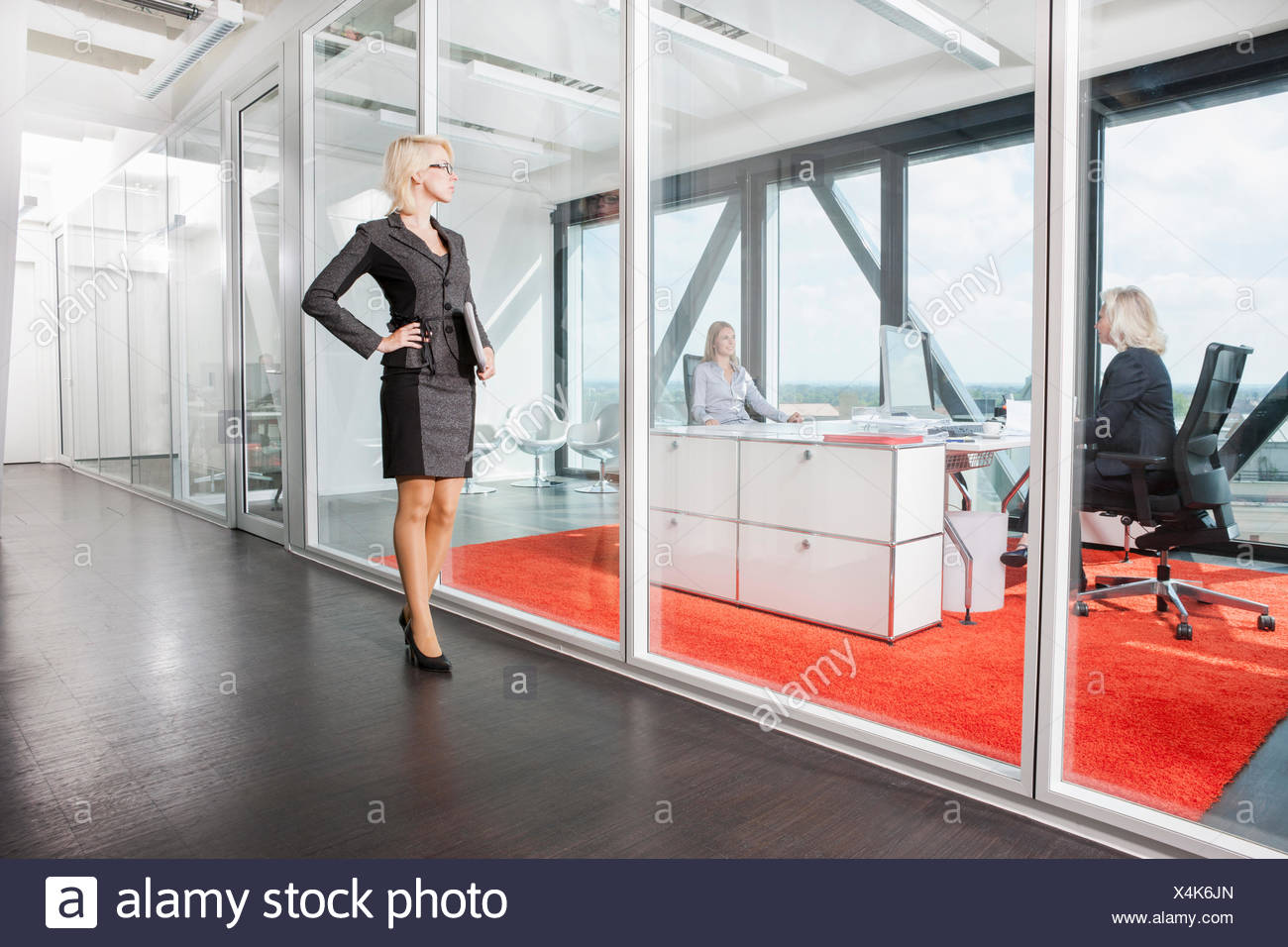 Mid adult woman standing outside interview room - Stock Image