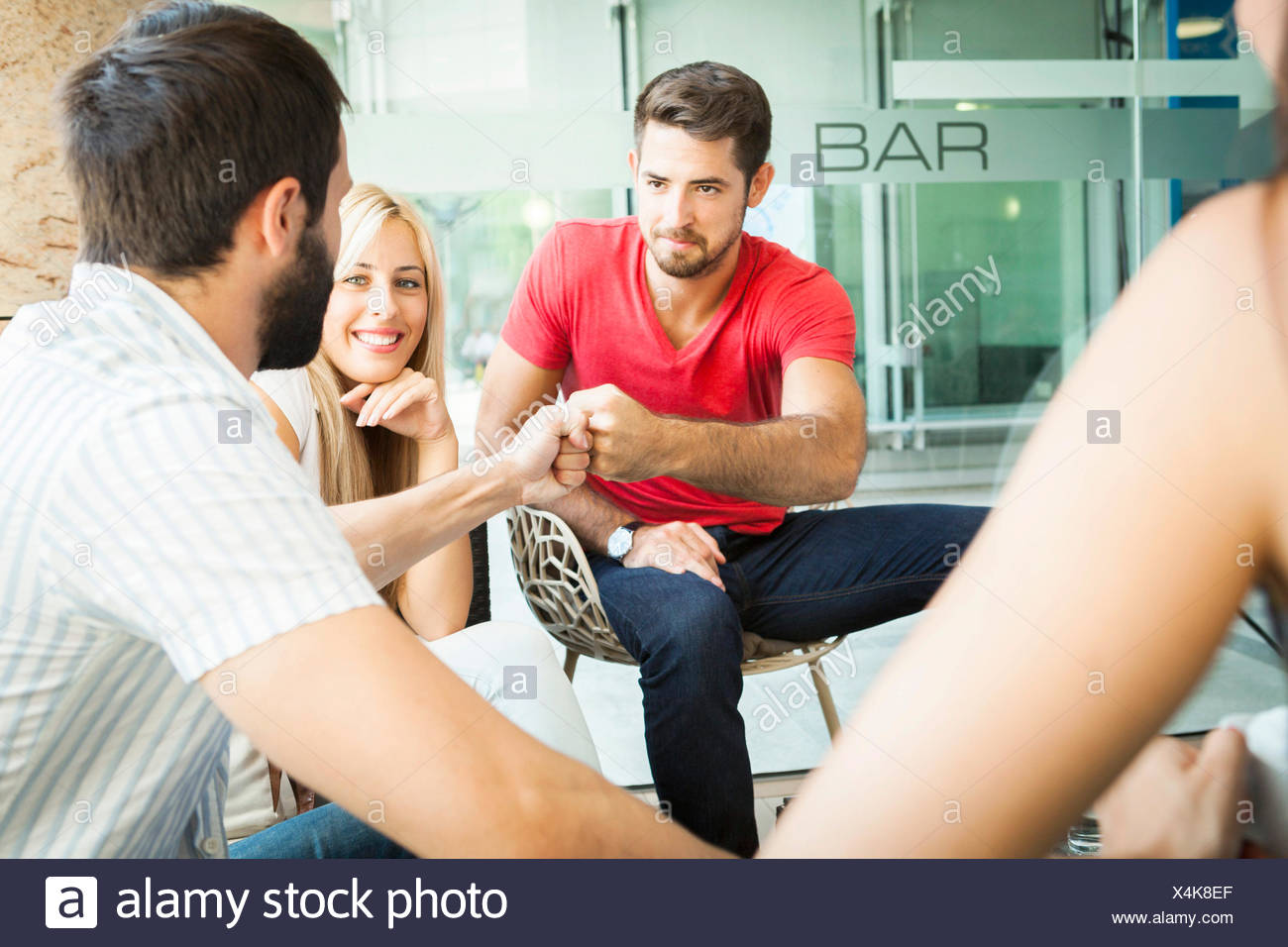 Two male students doing fist bump - Stock Image