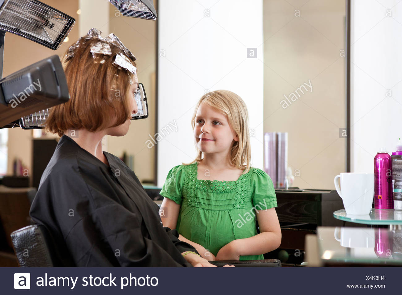 A young girl waiting in a hairdressing salon whilst her mother has her hair coloured - Stock Image