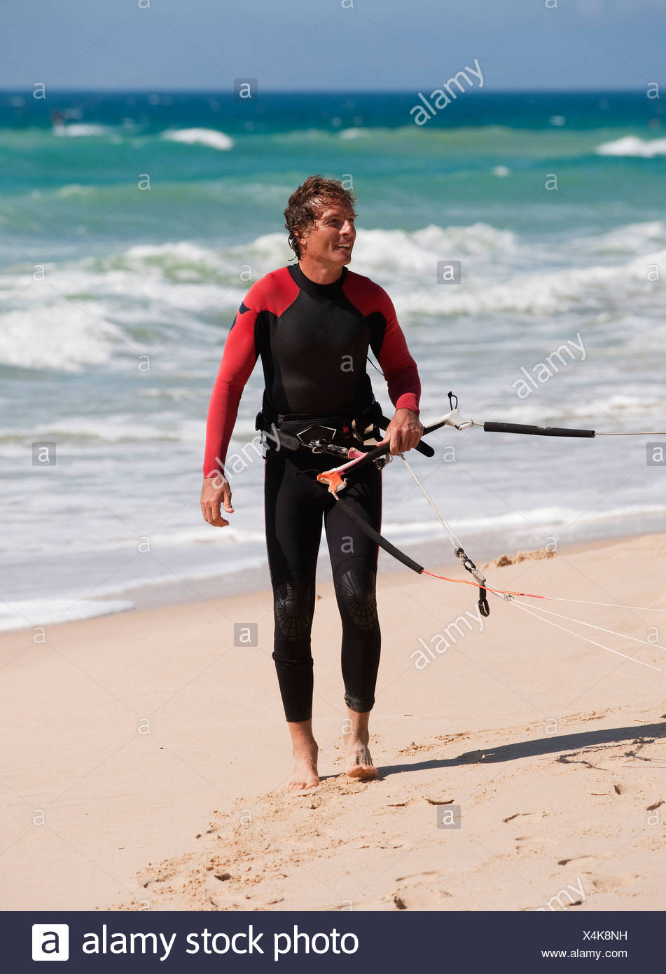 tarifa, cadiz, andalusia, spain; a man on punta paloma beach wearing a wetsuit and carrying kitesurfing equipment Stock Photo