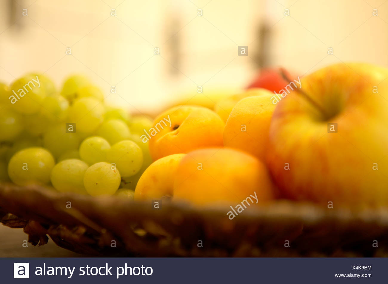 A basket of fruit on a table, close-up - Stock Image