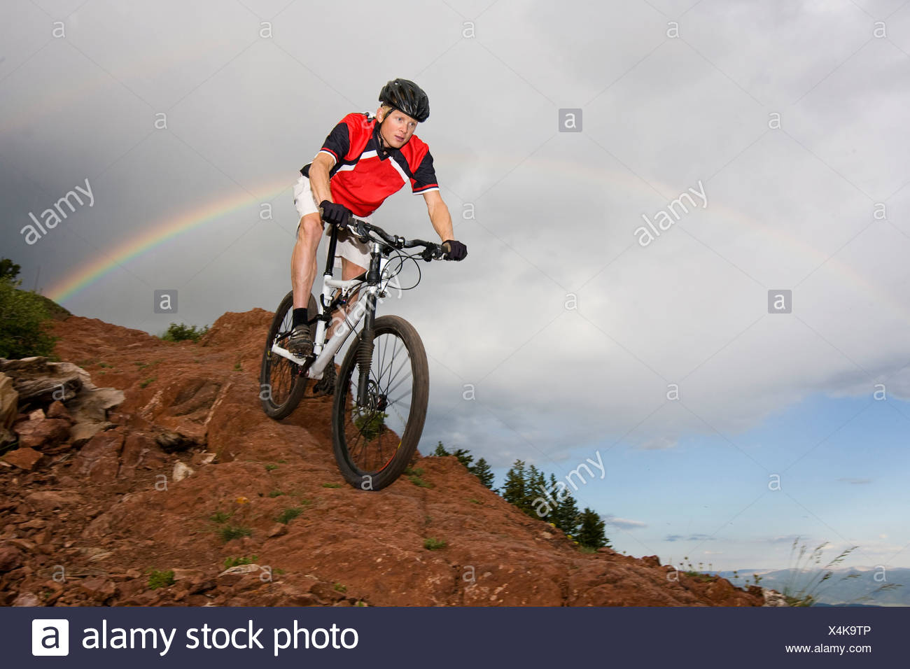 A man riding his bike under a rainbow on a rainy day in Utah. - Stock Image