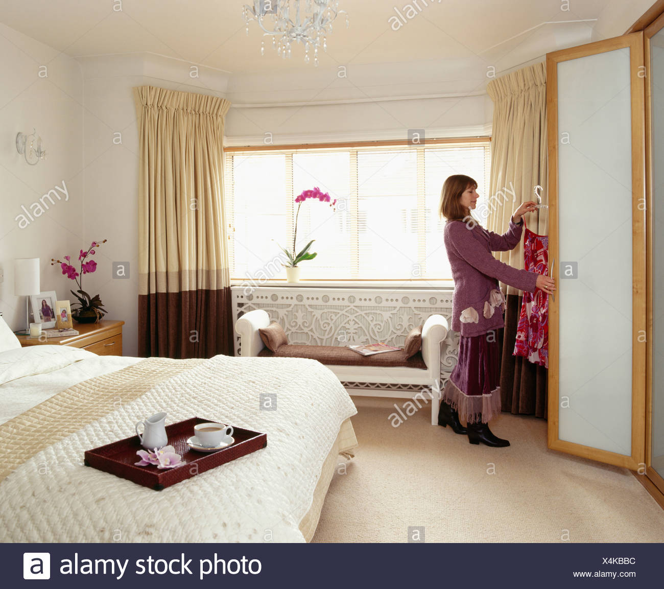 Picture of: Woman Putting Clothes Into Wardrobe In Modern Cream Bedroom Stock Photo Alamy