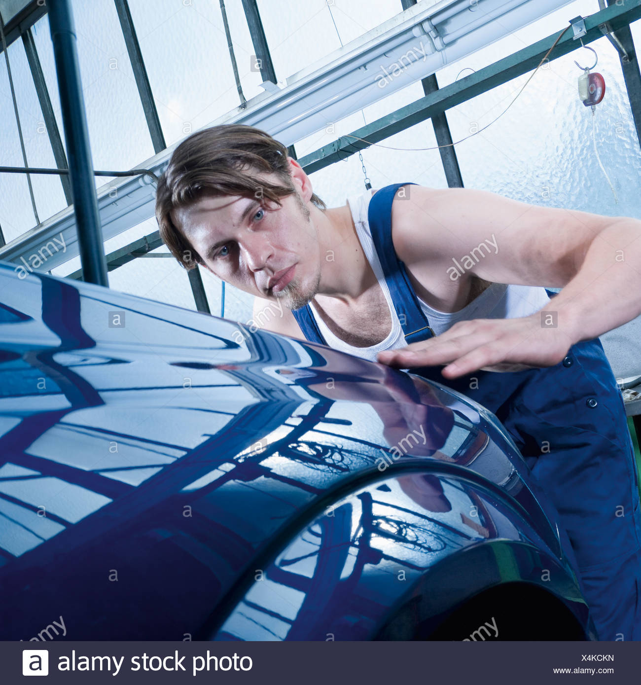 Germany, Augsburg, Worker looking at shiny car after waxing - Stock Image
