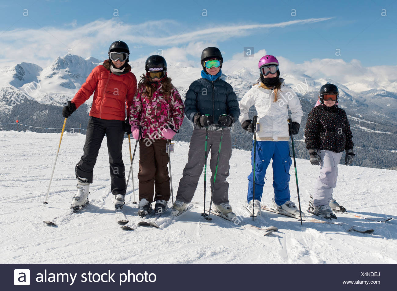a group of skiers posing with the mountains in the background; whistler british columbia canada - Stock Image