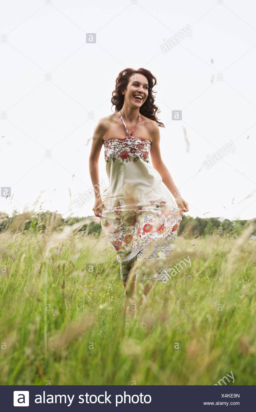 Woman running through wild meadow Stock Photo