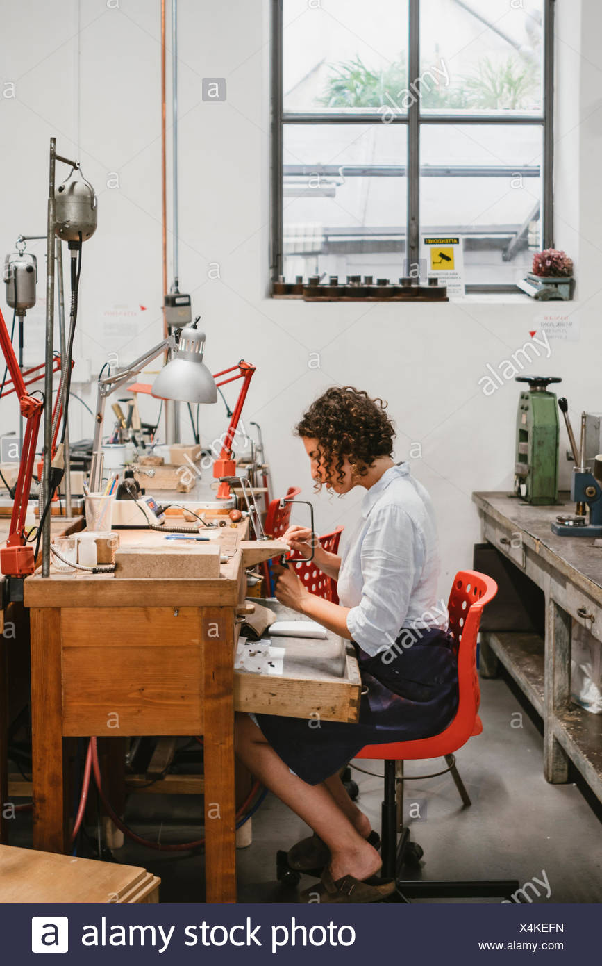 Female jeweller using coping saw at workbench - Stock Image