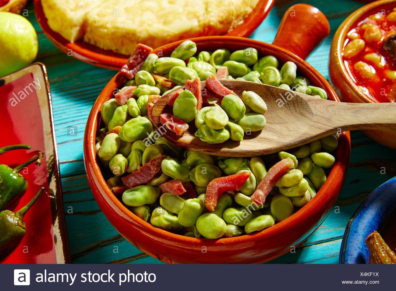 Tapas lima beans with iberico ham from Spain on wood. - Stock Image