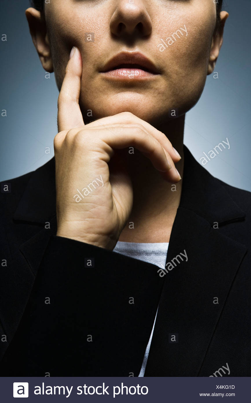 Businesswoman with hand held under chin deep in thought, portrait - Stock Image