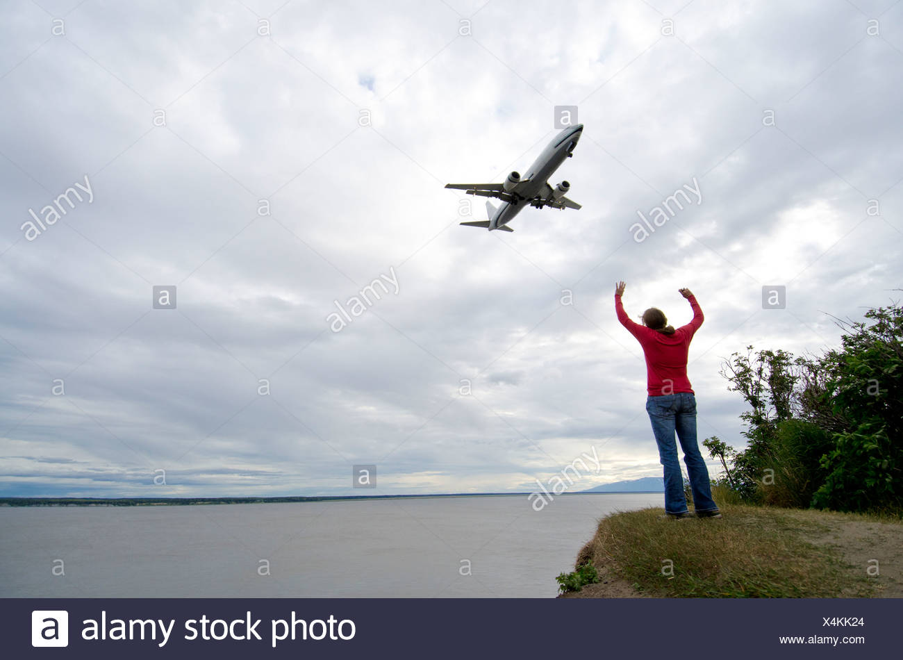 A young woman waves hello to a plane passing overhead in Anchorage, Alaska. - Stock Image