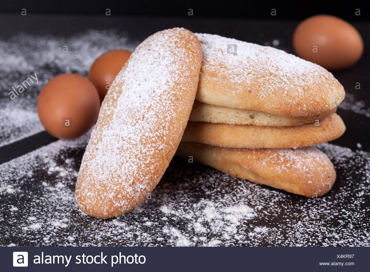Closeup of leavened savoiardi biscuits sprinkled with icing sugar. - Stock Image