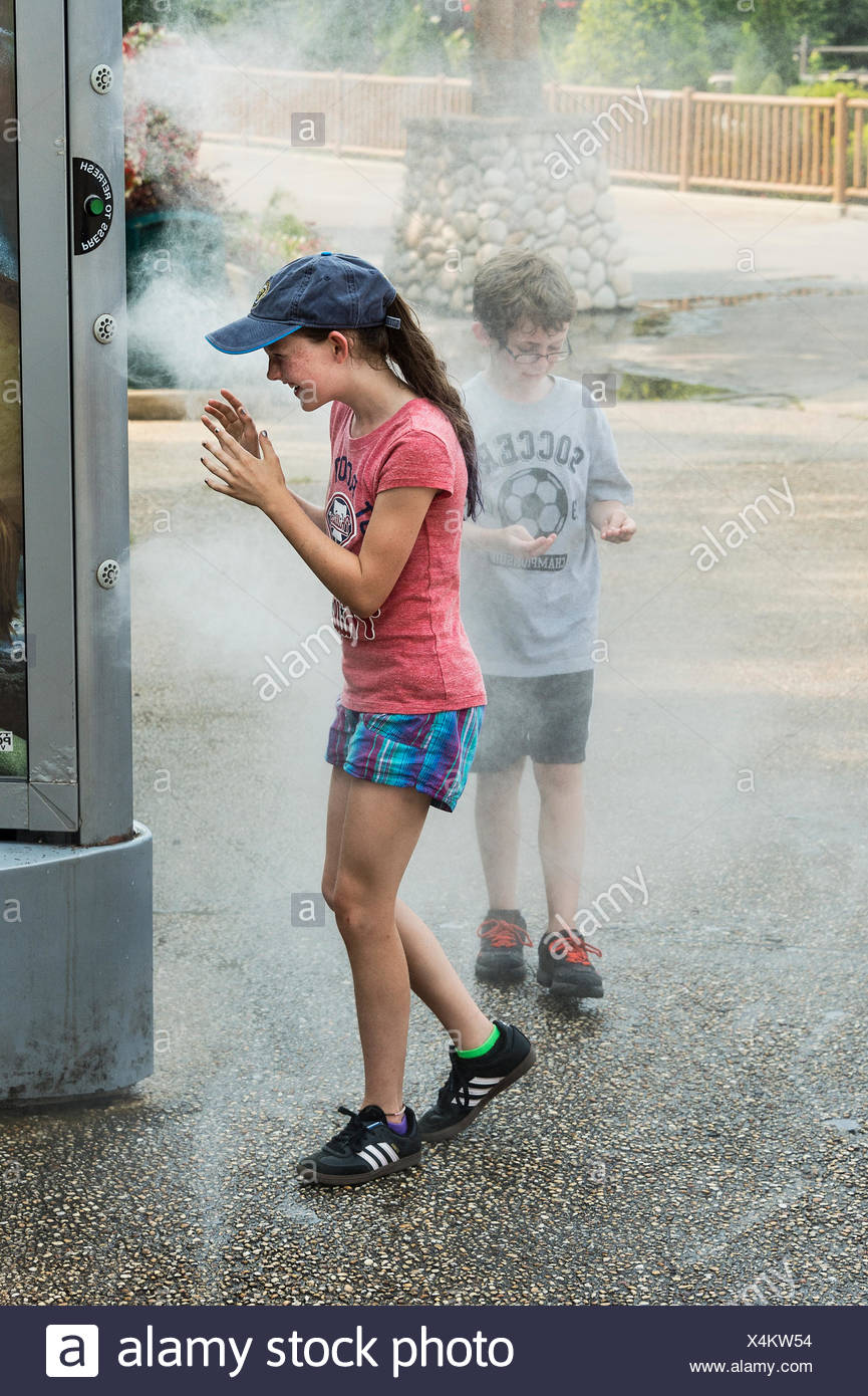 Kids cool off with the help of a refreshing mist machine at a park. - Stock Image