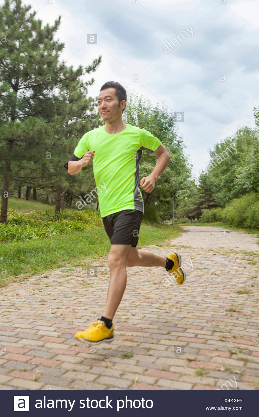 Young male runner running in park - Stock Image
