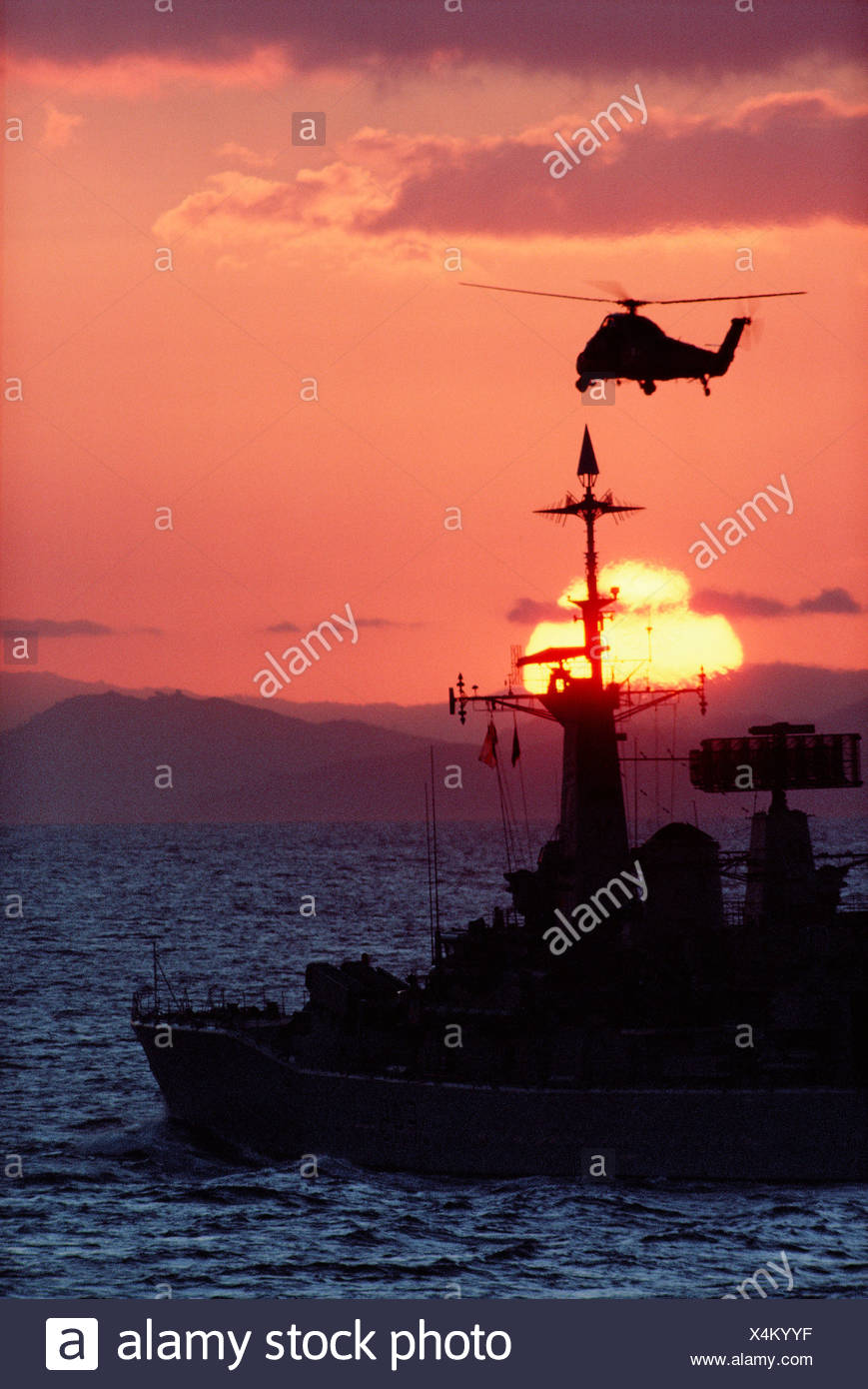 British Navy Warship HMS Minerva with hovering helicopter in sunset. Gulf War. 1991. Operation Desert Storm. - Stock Image