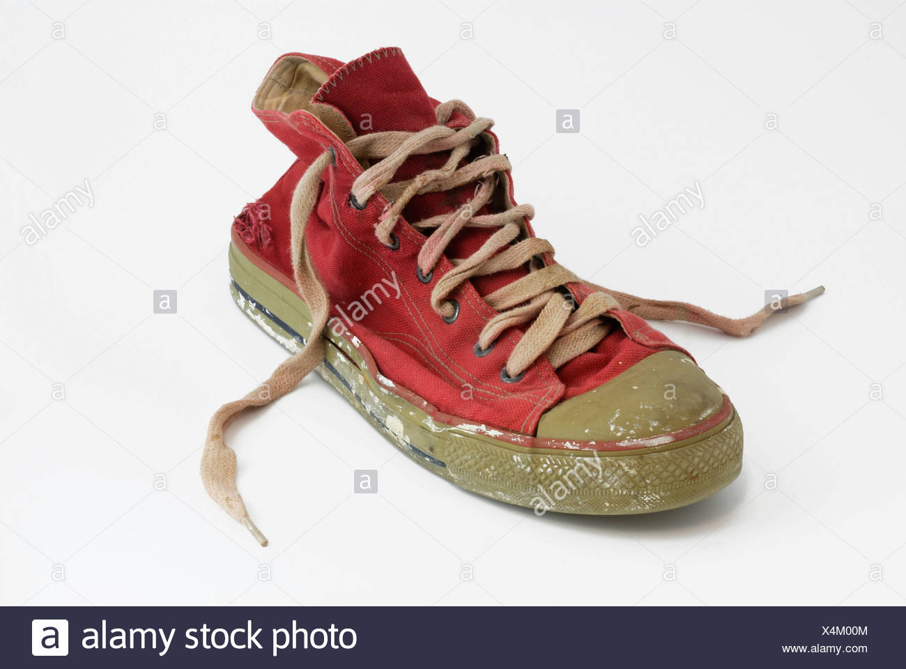 Worn-out red sneaker - Stock Image
