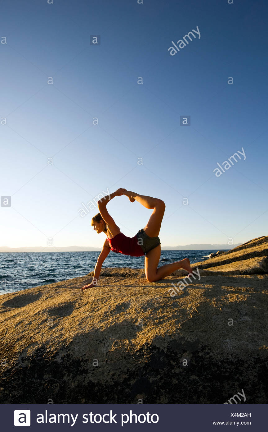 A young woman performs yoga on a granite boulder at sunset on the east shore of Lake Tahoe in the summer, NV. - Stock Image