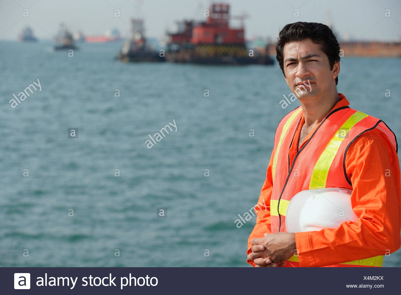 Man in work uniform working at port - Stock Image