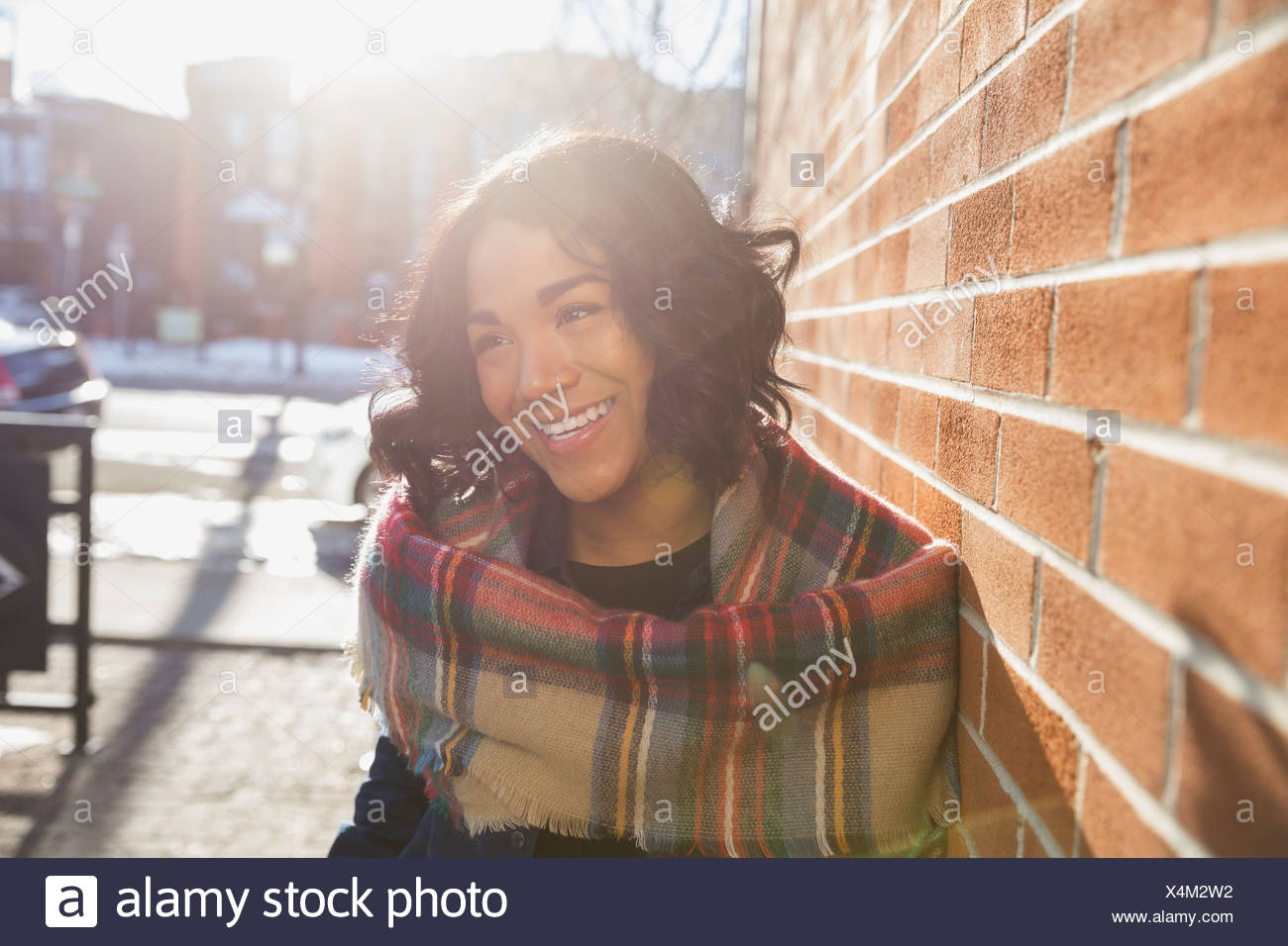 Smiling woman standing by brick wall - Stock Image