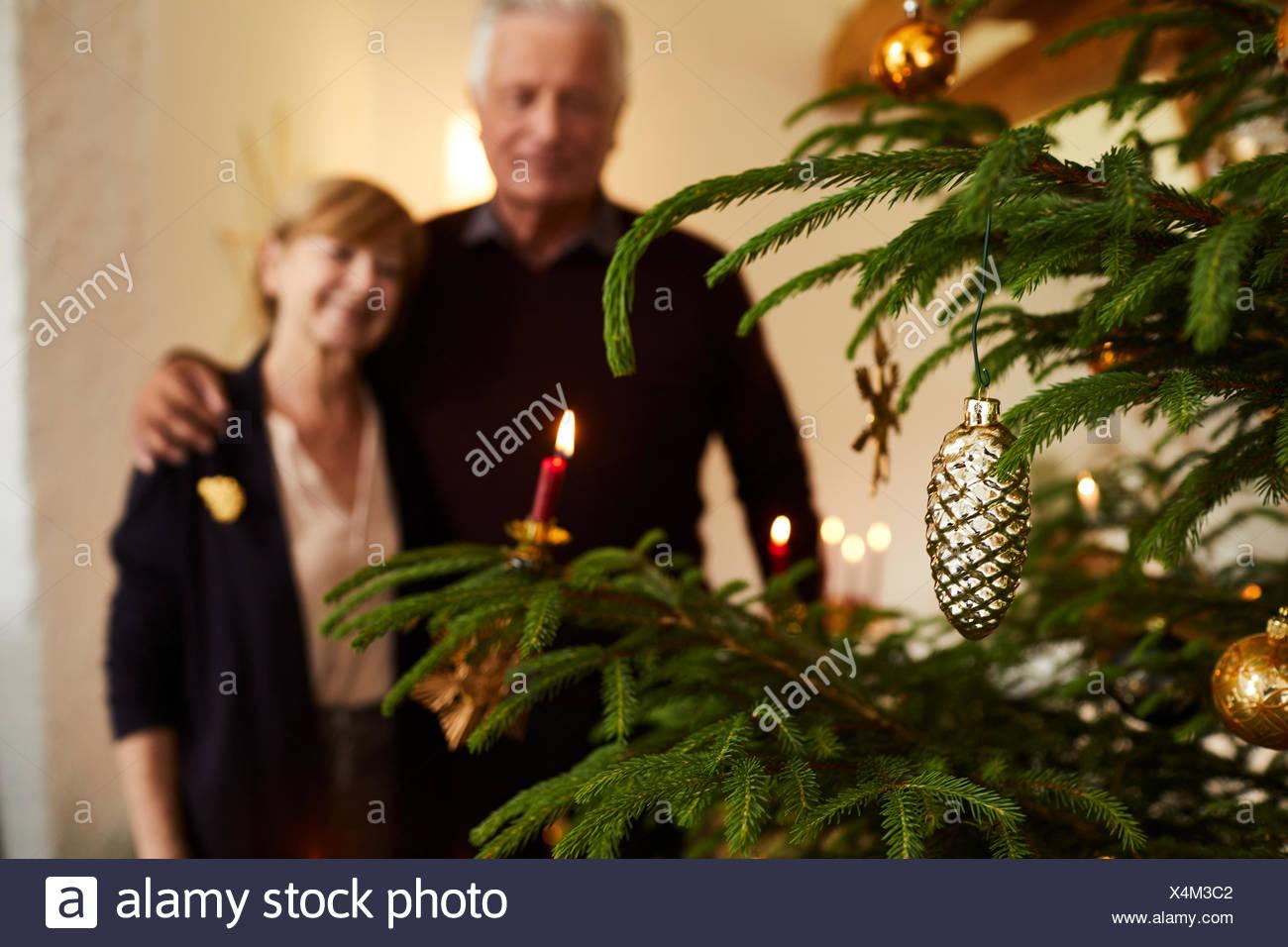 Senior couple in front of Christmas tree, half portrait Stock Photo
