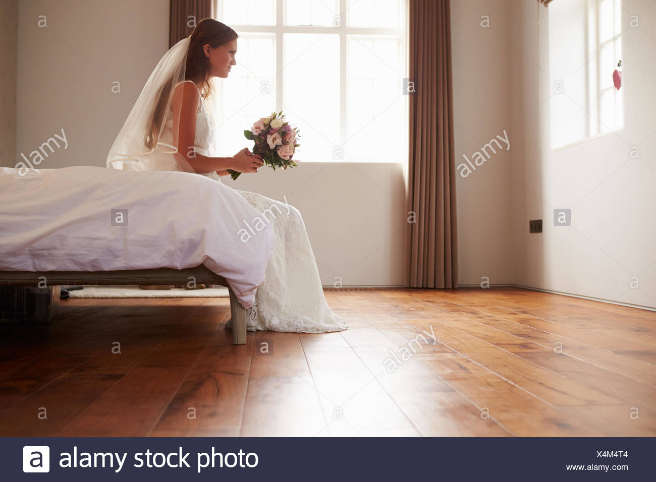 Bride In Bedroom Having Second Thoughts Before Wedding - Stock Image