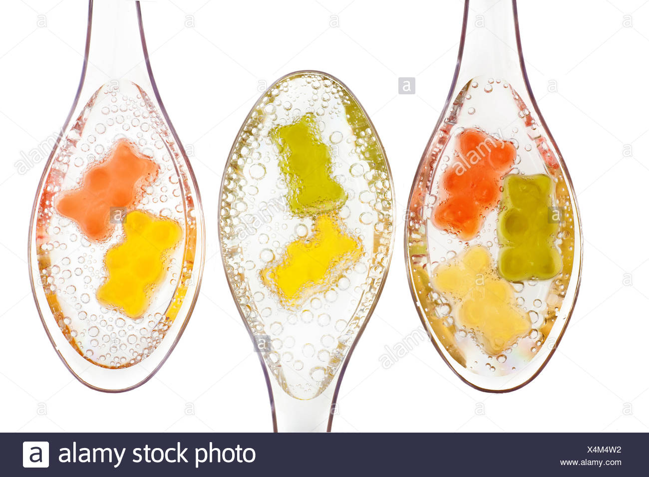 Gummi Bears in water on transparent spoons - Stock Image