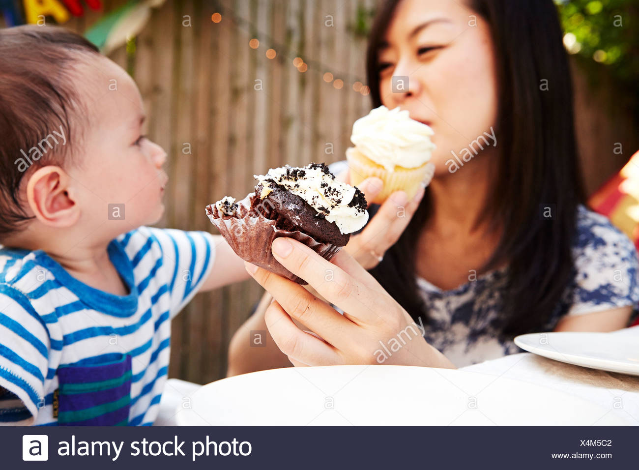 Mother and son feeding each-other cupcakes Stock Photo