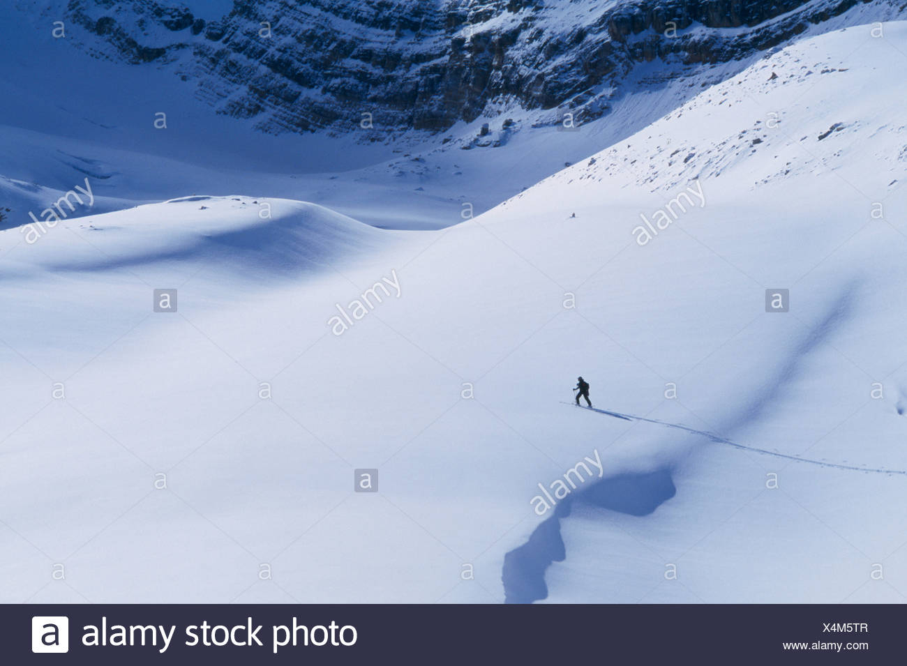 Solo skier skinning up a backcountry slope deep in the Canadian Rockies. - Stock Image