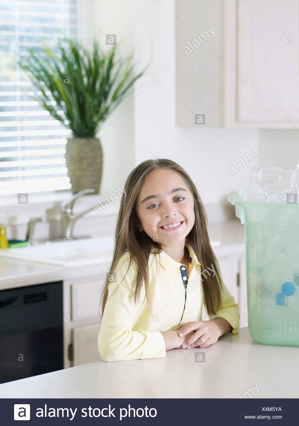 Young girl in kitchen with recyclable materials and bin smiling - Stock Image