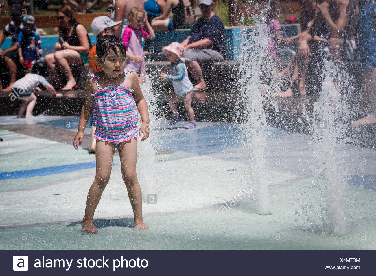 Barefoot girl approaching fountain at summer, people in background - Stock Image